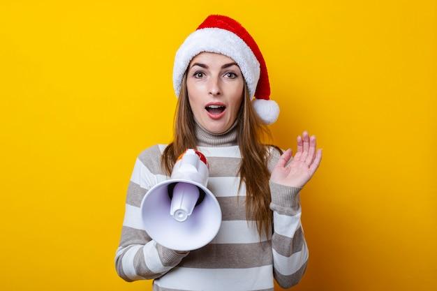 Удивленная молодая женщина в шляпе санта-клауса с мегафоном на желтом фоне.