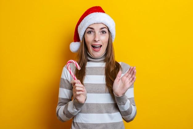 노란색 배경에 크리스마스 사탕과 함께 산타 클로스 모자에 놀란된 젊은 여자.