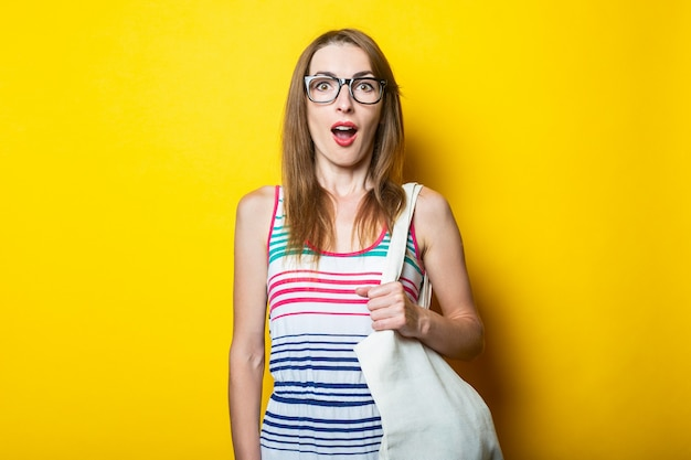 스트라이프 드레스, 안경 및 노란색 배경에 린넨 가방 놀란 된 젊은 여자.