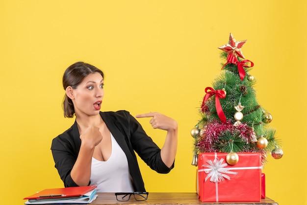黄色のオフィスで飾られたクリスマスツリーの近くに自分自身を指しているスーツを着て驚いた若い女性
