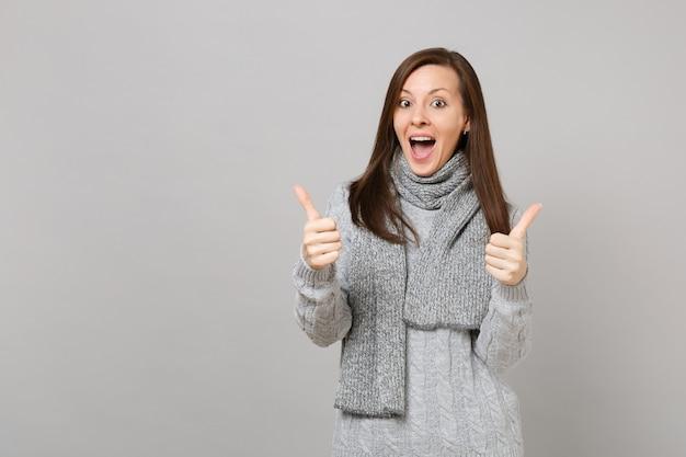 Удивленная молодая женщина в свитере, шарфе показывает большие пальцы руки вверх, держа рот широко открытым изолированным на серой предпосылке стены. эмоции людей здорового образа жизни моды, концепция холодного сезона. копируйте пространство для копирования.