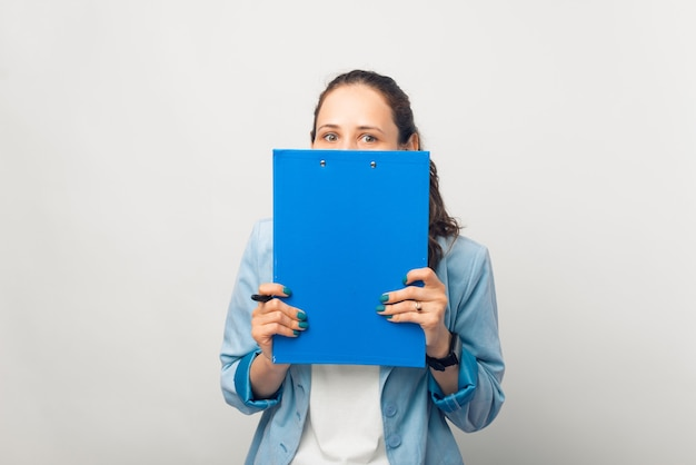Surprised young woman is hiding behind a paper board.