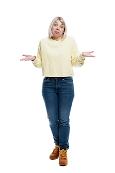 Surprised young woman in jeans and a yellow sweater. full height. isolated on white background. vertical.
