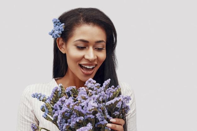 Удивленная молодая женщина смотрит на цветы и улыбается, стоя на сером фоне