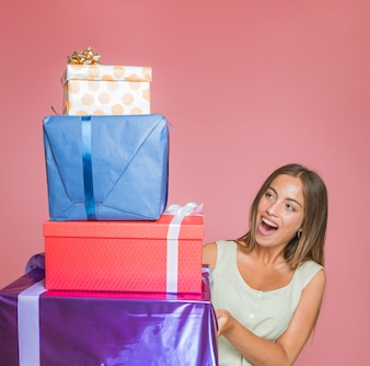 Surprised young woman looking at stack of gift box on colored background