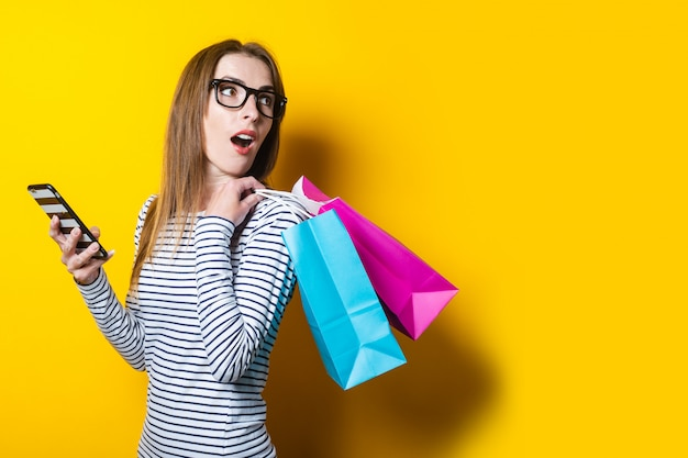 Surprised young woman looking back, holding a phone and shopping bags on a yellow background