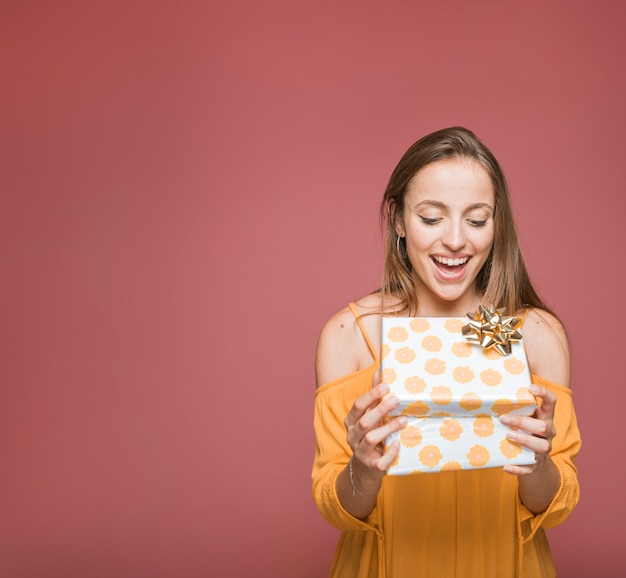 Surprised young woman looking at floral gift box on colored background