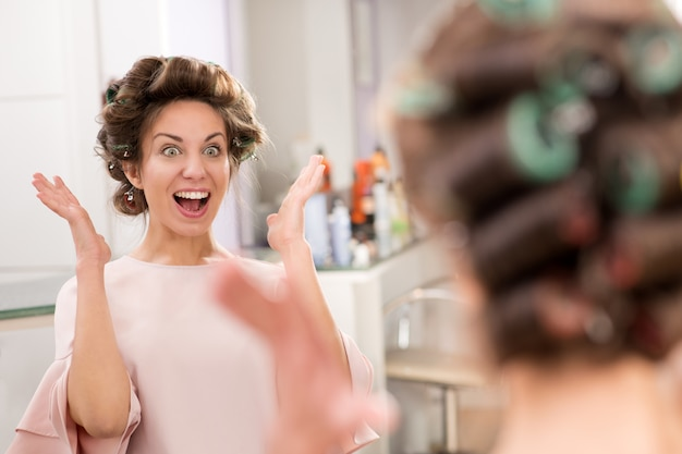 Surprised young woman looking at her new hairstyle
