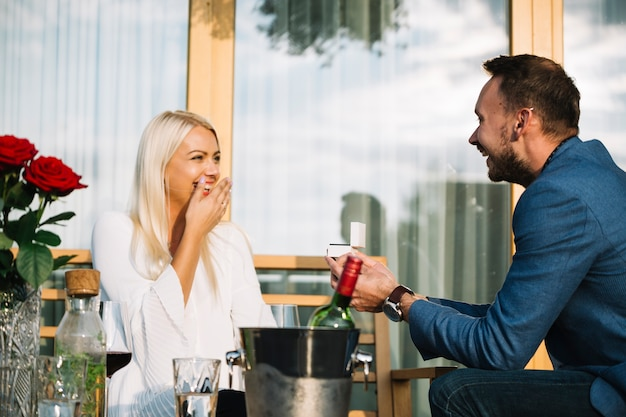 Surprised young woman looking at man giving engagement ring in restaurant
