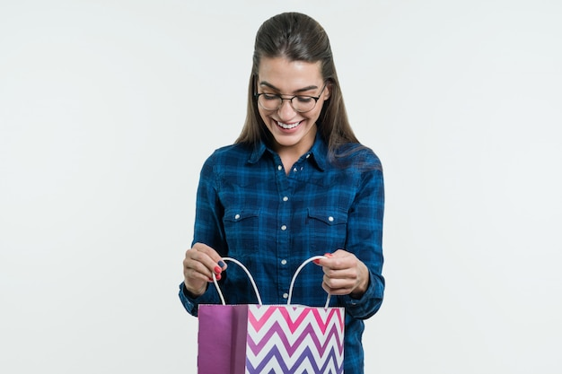 Surprised young woman looking shopping bag