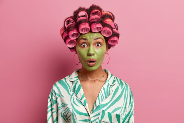 Surprised young woman looks in stupor, dressed casually, undergoes beauty procedures and makes perfect hairstyle, gets ready for party, wants to look beautiful, isolated on pink wall