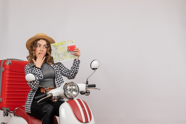 Surprised young woman on moped holding card and map on grey