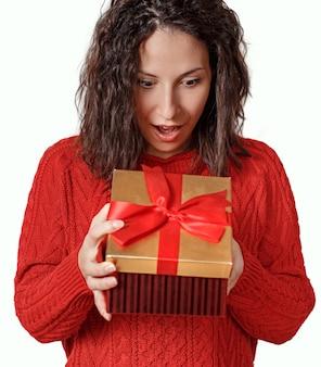 Удивленная молодая женщина, открывающая подарочную коробку
