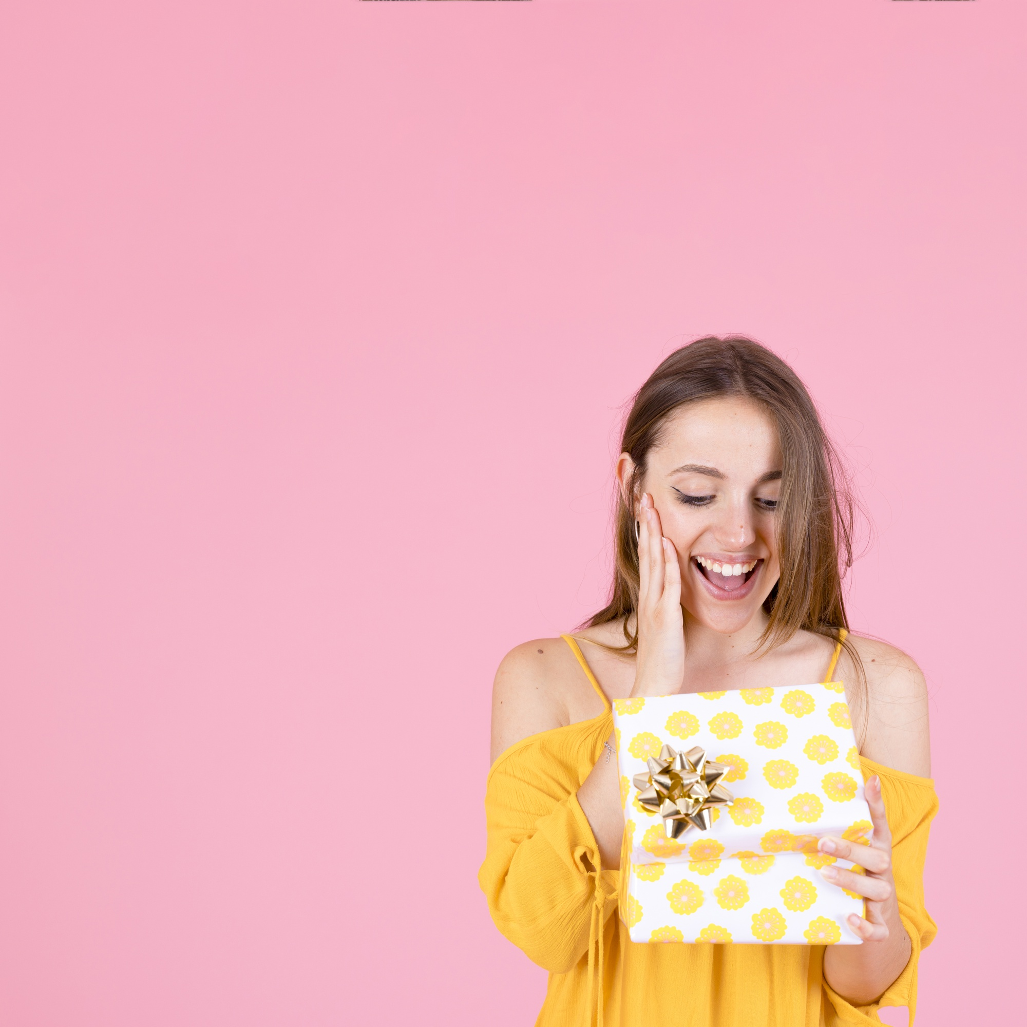 Surprised young woman opening yellow polka dot present box with golden bow