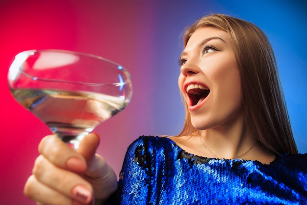 The surprised young woman in party clothes posing with glass of wine.