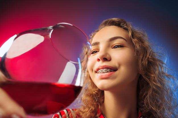 Giovane donna sorpresa in abiti da festa in posa con un bicchiere di vino