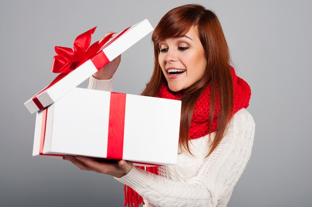 Giovane donna sorpresa che dà una occhiata al regalo di natale