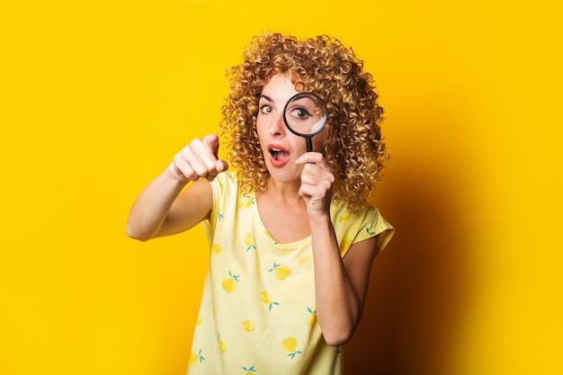 노란색 표면에 돋보기를 통해 보이는 그녀의 손가락을 가리키는 놀란 젊은 여자