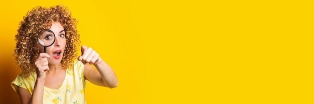 Surprised young woman pointing her finger looks through a magnifying glass on a yellow surface