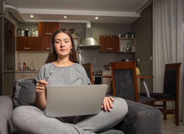 Surprised young woman and pregnancy test with laptop, woman looking for information about pregnancy on internet with laptop