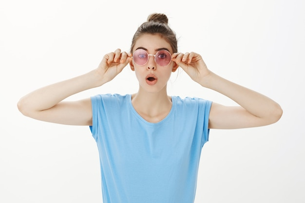 Surprised young woman put on pink sunglasses and looking amazed