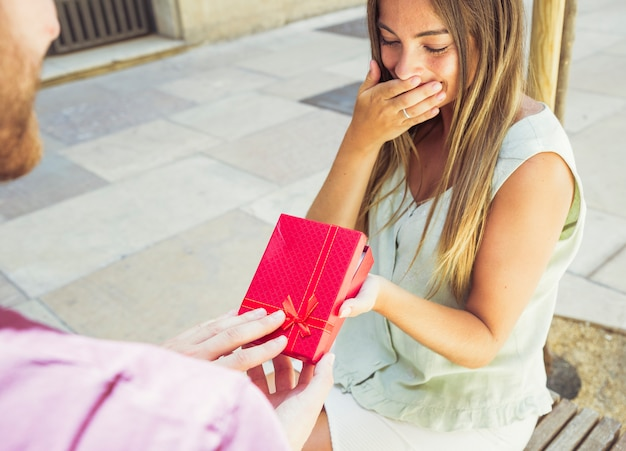 Surprised young woman receiving gift from her boyfriend