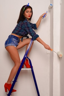 Surprised young woman in a shirt and shorts paints a wall with two paintballs standing on a ladder