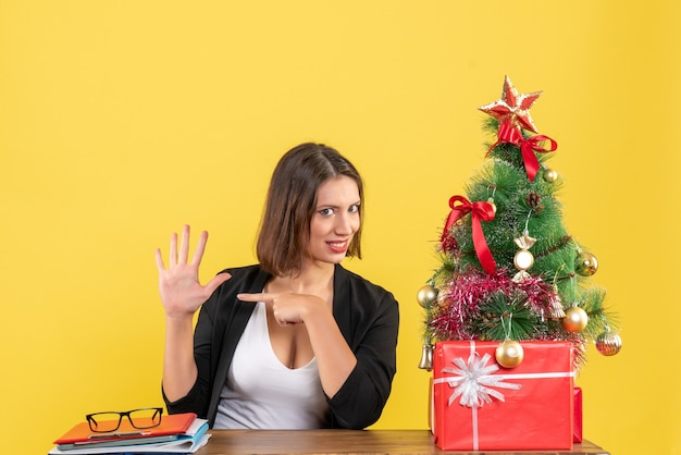 黄色のオフィスで飾られたクリスマスツリーの近くでスーツを着て5を示す驚いた若い女性