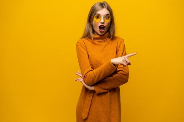 Удивленная молодая женщина, стоящая и указывая на желтую стену