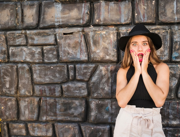 Surprised young woman standing in front of wall