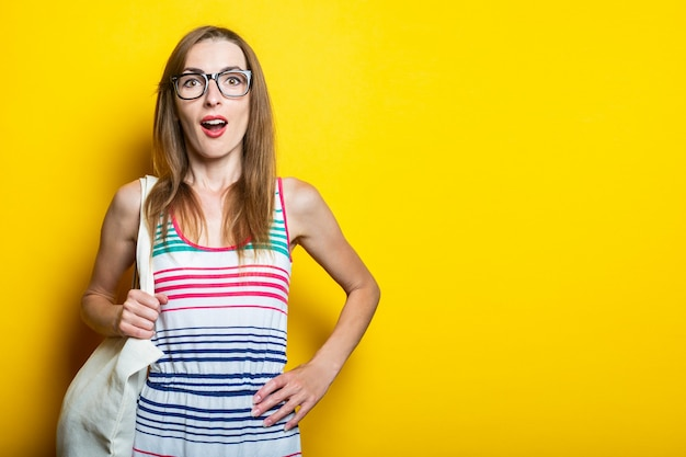 Surprised young woman in striped dress, glasses and with linen bag on yellow background.