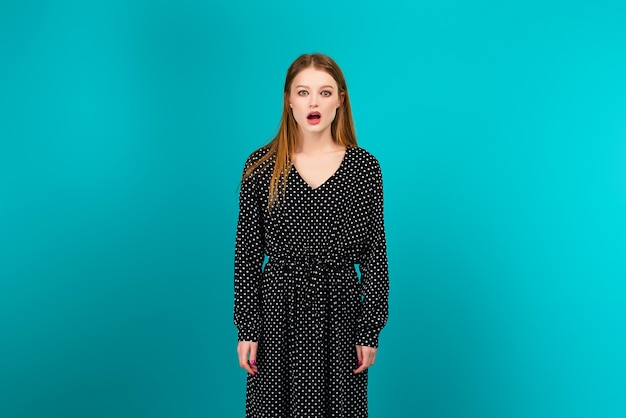 Surprised young woman in a summer dress isolated over turquoise blue background