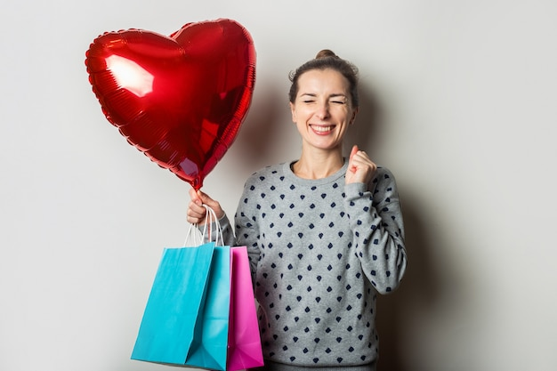 Surprised young woman in a sweater holds a poarok for and heart air balloon and rejoices at the gift on a light background. valentine's day concept. banner.