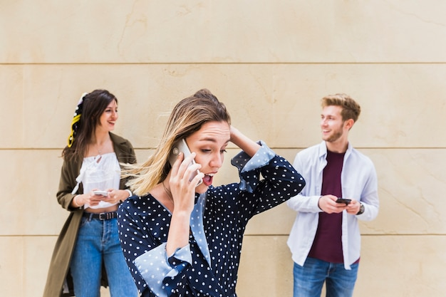 Surprised young woman talking on mobile phone standing in front of friends looking at each other
