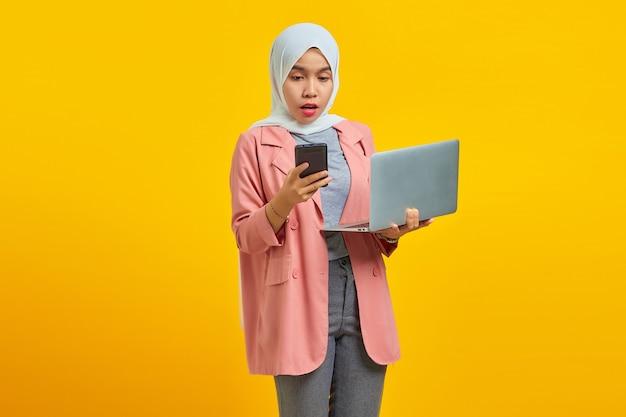 노란색 배경에 격리된 채 노트북과 휴대전화를 사용하는 놀란 젊은 여성