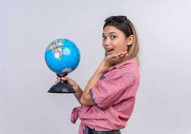 A surprised young woman wearing red shirt holding a globe while looking