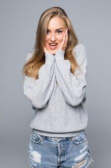 Giovane donna sorpresa che indossa un maglione caldo su sfondo grigio