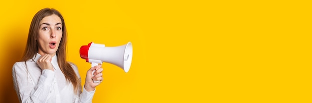 Surprised young woman in a white shirt holds a megaphone on a yellow background