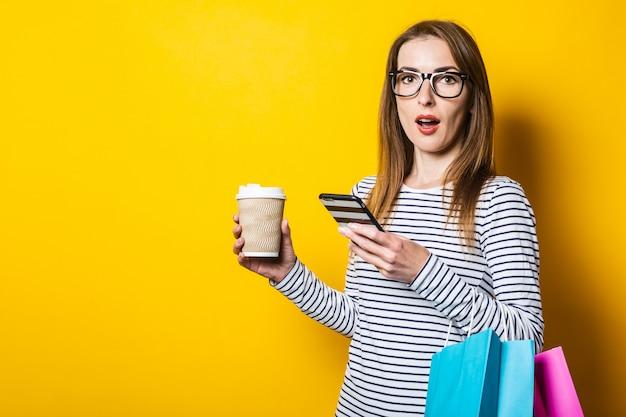 黄色の背景に紙コップで、ショッピングバッグの電話で驚いたの若い女性