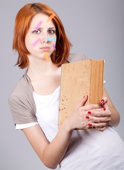 Surprised young woman with book and  notes on face. portrait on grey background