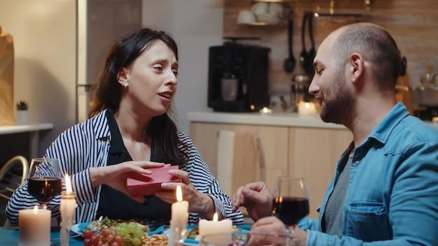 작은 선물 상자를 여는 부엌 테이블에 앉아 있는 매력적인 미소를 가진 놀란 젊은 여성. 집에서 함께 식사하고, 식사를 즐기고, 기념일을 축하하는 쾌활한 커플