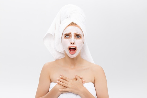 Surprised young woman with cosmetic mask for the face