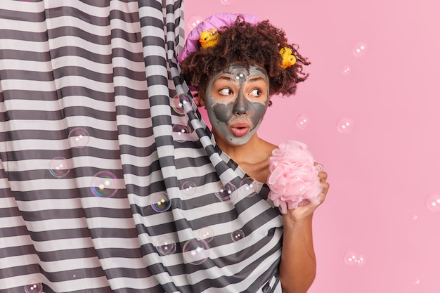 Surprised young woman with curly hair applies beauty clay mask on face looks aside holds shower sponge enjoys showering poses in douche hides behind curtain soap bubbles around