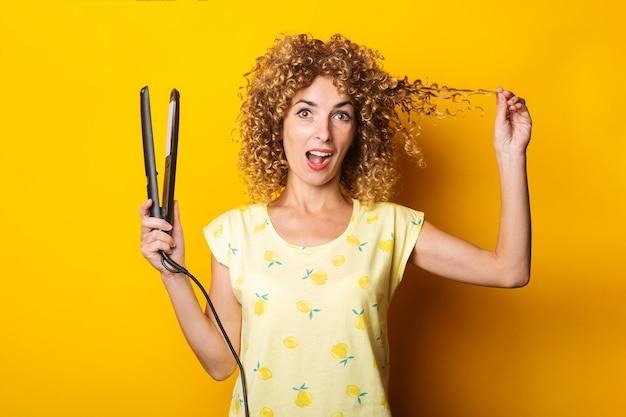 黄色の背景にストレートヘアアイロンで巻き毛の若い女性を驚かせた。
