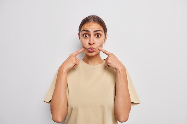 어두운 빗질 머리를 가진 놀란 젊은 여성은 뺨에 공기를 머금고 얼굴에 검지 손가락을 대고 흰 벽에 격리된 캐주얼한 베이지색 티셔츠를 입고 장난꾸러기 표정을 하고 있다
