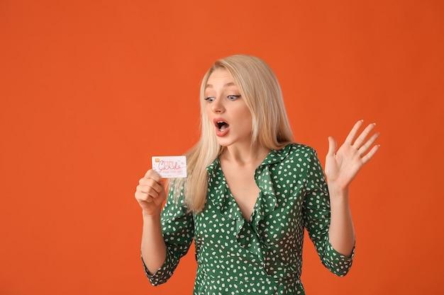 색상 배경에 선물 카드와 함께 놀된 젊은 여자
