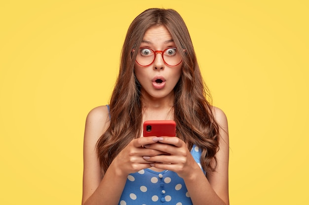 Surprised young woman with glasses posing against the yellow wall