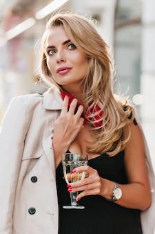 ワイングラスを持って遠くを見ている、軽く日焼けした肌の驚いた若い女性。ぼかし通りに立っている肩にスタイリッシュなコートを着た華やかな金髪の女性モデル