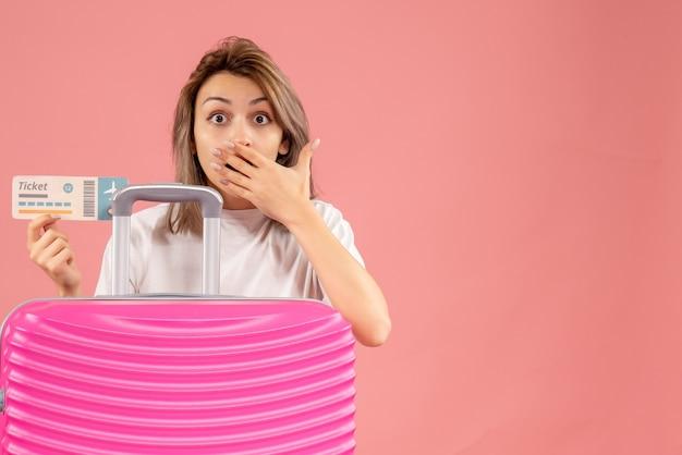 チケットを持っているピンクのスーツケースを持つ驚いた若い女性