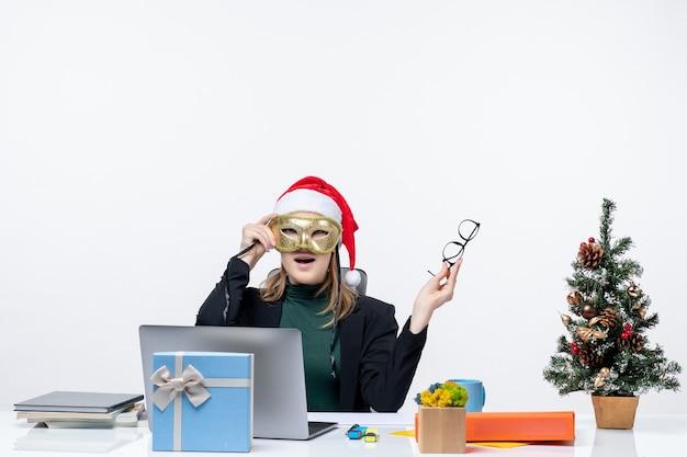 Giovane donna sorpresa con il cappello di babbo natale che tiene gli occhiali e maschera da portare seduto a un tavolo con un albero di natale e un regalo su di esso in ufficio su priorità bassa bianca